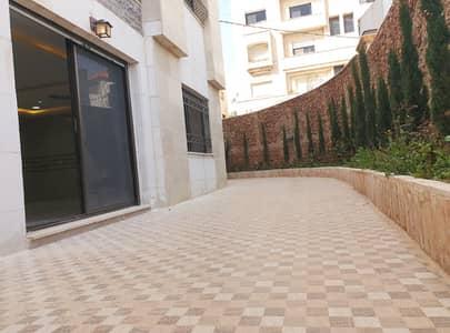 فلیٹ 4 غرف نوم للبيع في أم أذينة، عمان - شقة طابقية شبه أرضي مع ترس واسع وحديقة في أم أذينة